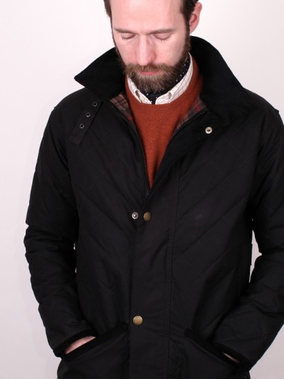 Man in cravat and wax jacket looking down